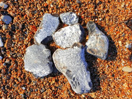 Edged flints in the sand on the Baltic Sea