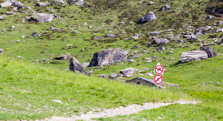 Sign pedestrians and riders on horseback is prohibited on the bike path runs along the alpine meadow near Tignes, French Alps. photo