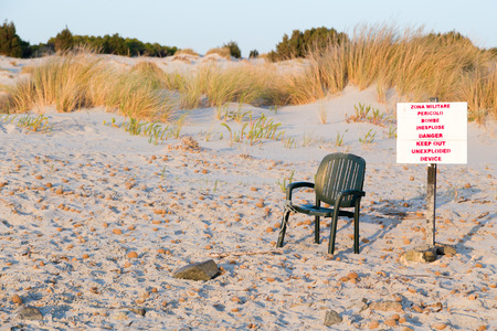 broken chair: Prohibiting the plate with a broken chair on a deserted sandy beach.