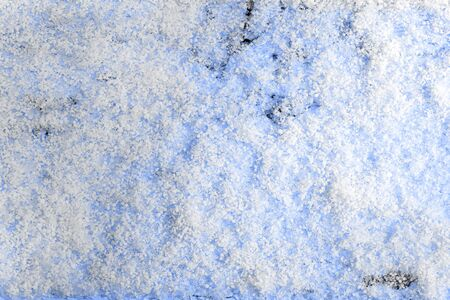 christmas grounds: Snow clumps close-up on a blue wooden surface Stock Photo