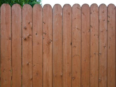 Brown painted wooden fence with round coners