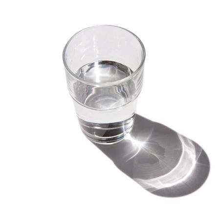 Half full glass of clear still water with drop refracting shadow