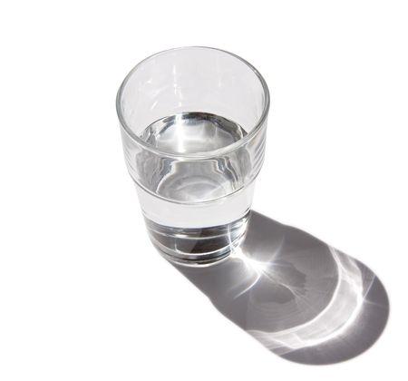 agua purificada: La mitad vidrio lleno de agua clara con gota refractor sombra  Foto de archivo