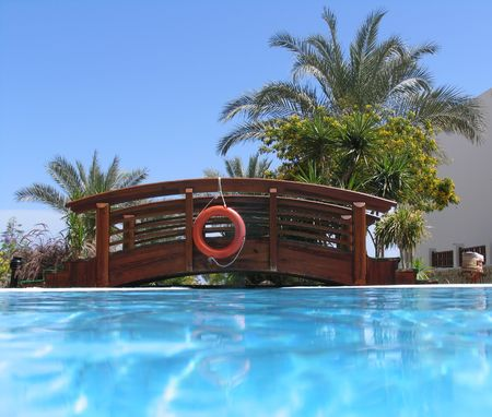 Bridge over the swimming pool with life buoy, palms and clear sky Stock Photo