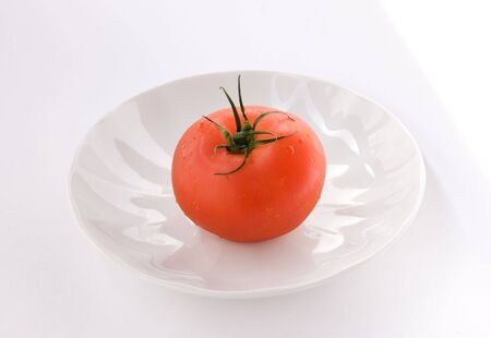 Ripe red tomato on white plate (clipping path on tomato)
