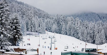 Ski slope and chair ski lift at Borovets, Bulgaria in snowing cloudy day Stock Photo