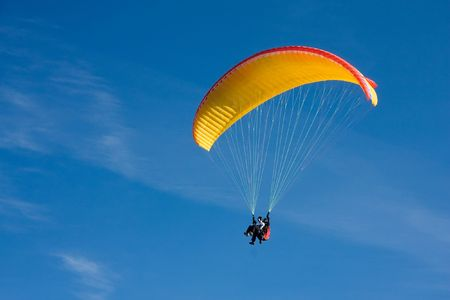 Paragliding in Bulgaria over the mountains against clear blue sky Stock Photo