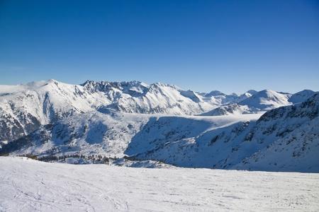 Ski slope and panorama of winter mountains. Alpine ski resort Bansko, Bulgaria photo