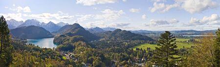 schwangau: Panoramic view of Bavarian Alps, mountain lake and Hohenschwangau from Neuschwanstein castle. Schwangau, Germany.