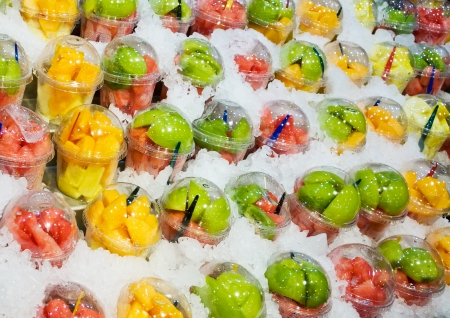 Fresh fruit mix in plastic caps on ice photo