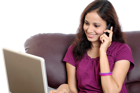 phonecall: Smiling young woman working with laptop and talking on cellphone Stock Photo