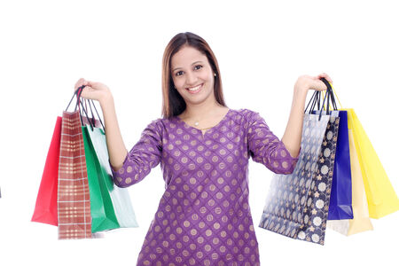 carrying girl: Young woman holding shopping bags against a white background  Stock Photo