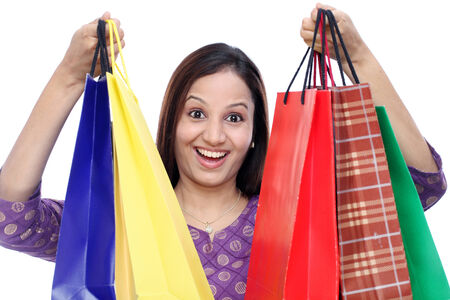 carrying girl: Cheerful Indian woman with shopping bags against white background