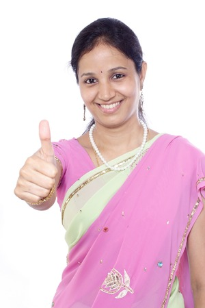 Young happy Indian woman showing thumbs up against white Stock Photo