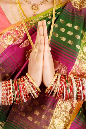 Traditional Indian girl holding hands in prayer position photo