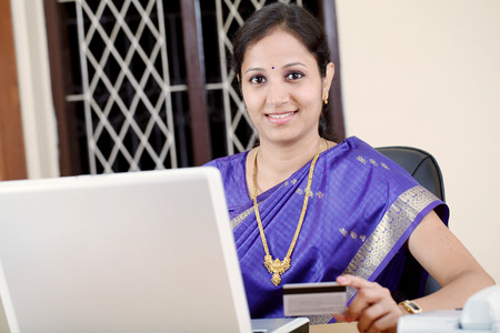 Beautiful Indian traditonal woman online shopping at home photo
