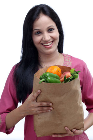 Young Indian woman holding grocery bag with full of fruits and vegetables photo