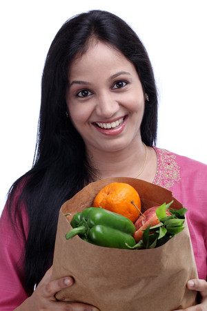 Happy young Indian woman holding grocery bag with full of fruits and vegetables photo