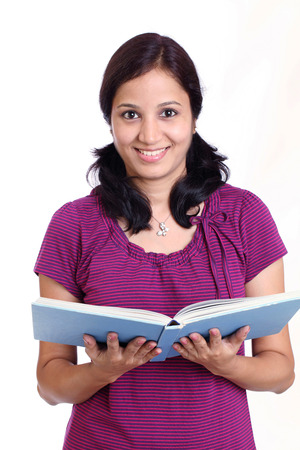 Smiling Indian female student holding books against white background