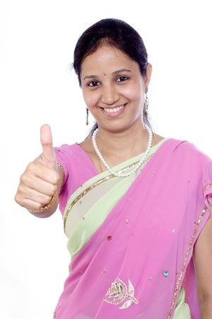 Young traditional Indian woman showing thumbs up against white background photo