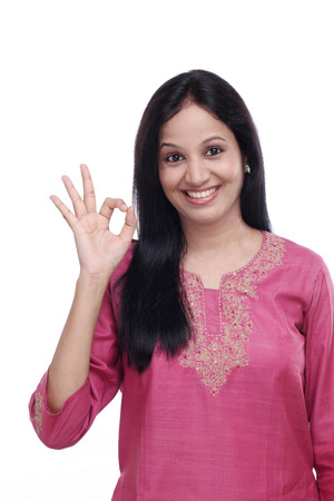 Young indian girl showing OK sign against white background Stock Photo