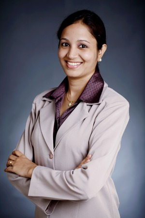 Happy Indian Business woman with arms crossed on grey background photo