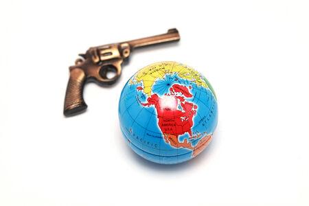 Toy gun and globe on white background photo