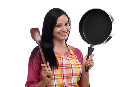 Young Indian woman holding kitchen utensil against white  photo