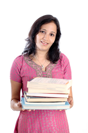 Young female college student holding stack of books against white photo
