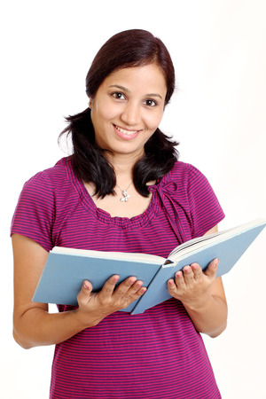 fresh graduate: Smiling Indian female student holding books against white