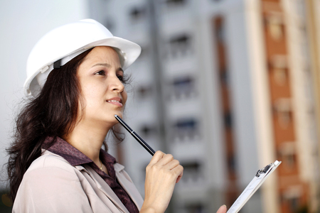 Indian Female construction engineer thinking at work place photo