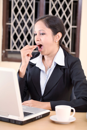 Pretty Indian business woman yawning in the office photo