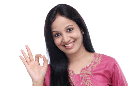 Young Indian woman showing OK sign against white