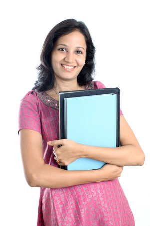 Smiling Indian female student holding books against white background  photo