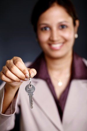 Smiling young business woman showing a key photo