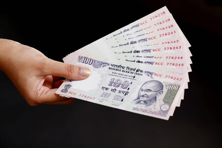 rupee: Hand holding hundred rupee bank notes against black  Stock Photo