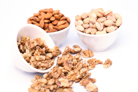 Bowls of Almond,pistachios and wall nuts on white  photo