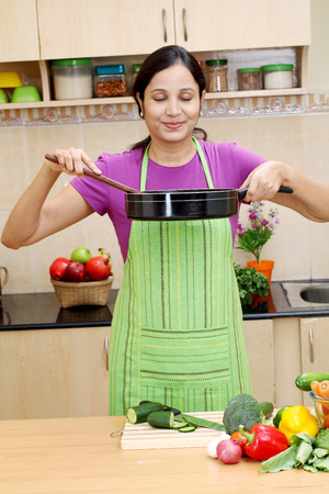 Young Indian woman preparing a dish in her kitchen  photo