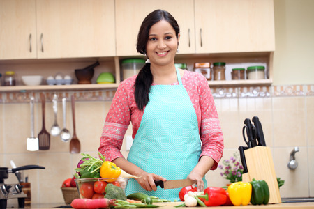 Young Indian woman cutting vegetables in kitchen room