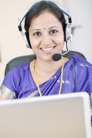 Happy Indian business woman with headphones photo