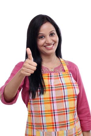 Mujer india joven feliz vistiendo delantal de cocina y mostrando los pulgares para arriba Foto de archivo
