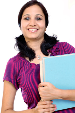 Smiling young female student against white background photo