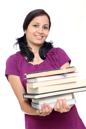 Smiling Indian female student holding books against white  photo