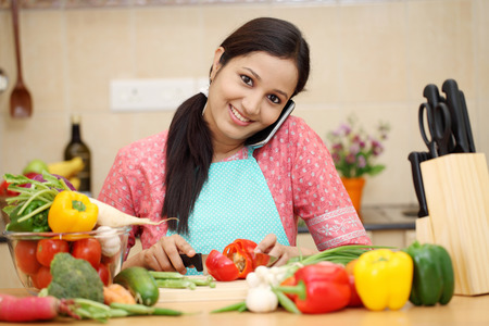 Smiling young woman cutting vegetables and talking on cellphone Stock Photo