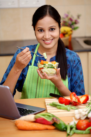 Young Indian woman with kitchen apron and eating salad Stock Photo