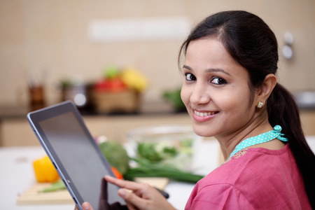 indian women: Young Indian woman using a tablet computer in her kitchen  Stock Photo