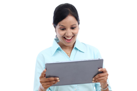 Excited young business woman looking at touch pad PC against white background photo