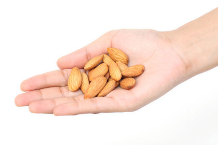 Handful of almonds against white background