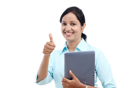 thumbsup: Young business woman with tablet and making thumbs up gesture against white