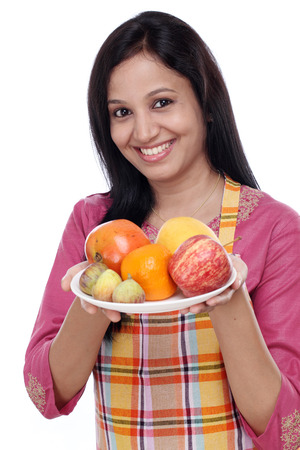 Young happy smiling woman with plate of fruits photo